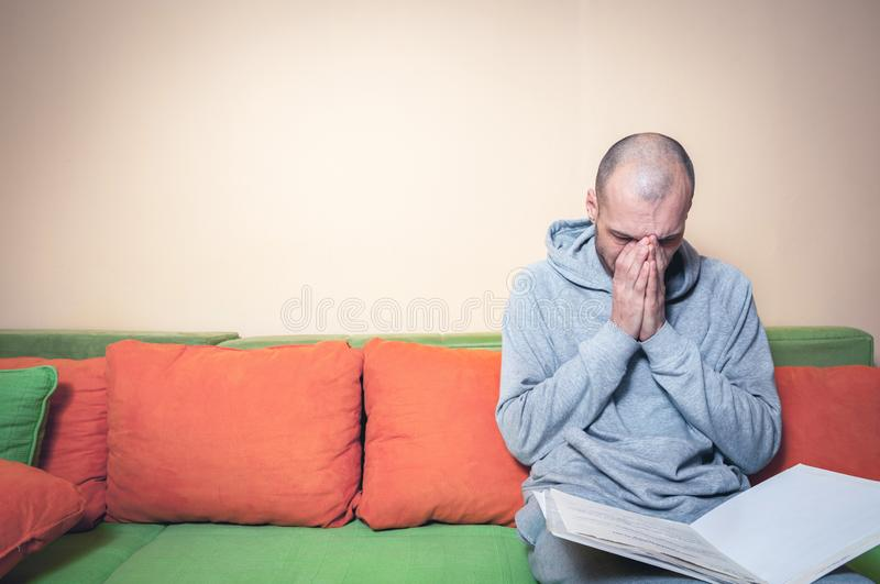 Young or middle age sick man in the casual clothes reading medic results on the papers from his doctor and realize that he have a. Sick or ill man. Young or stock images