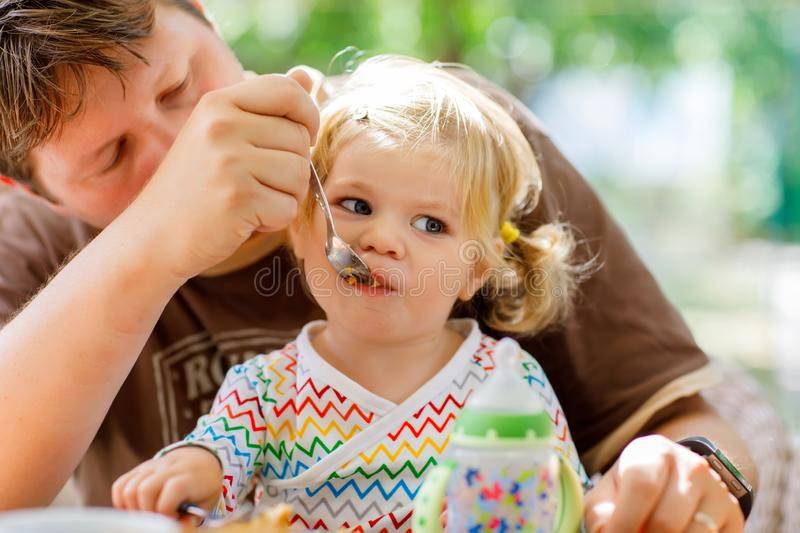 Young middle-aged father feeding cute little toddler girl in restaurant. Adorable baby child learning eating from spoon stock images