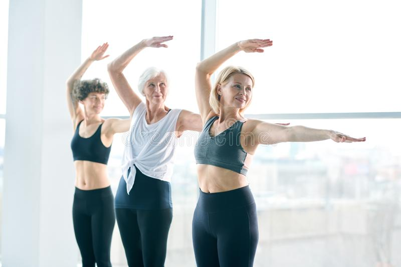 Active females. Young, middle aged and senior females in activewear standing in row while practicing exercise for stretching stock photo