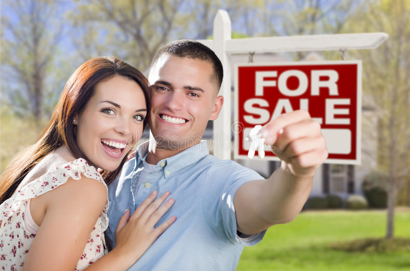 Young Military Couple In Front of Home, House Keys, Sign. Mixed Race Excited Military Couple In Front of New Home with New House Keys and For Sale Real Estate stock photo