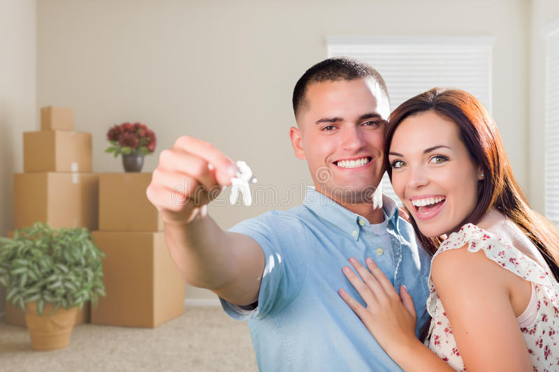 Young Military Couple with House Keys in Empty Room with Packed. Happy Young Military Couple with House Keys in Empty Room with Packed Moving and Potted Plants royalty free stock images
