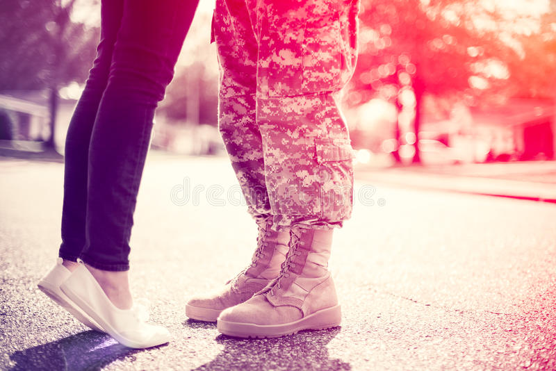 Young military couple kissing each other, homecoming concept. Soft focus, cross process toning applied, light leak in the corner royalty free stock image