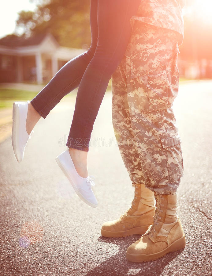 Young military couple kissing each other, homecoming concept. Warm orange toning applied royalty free stock photo