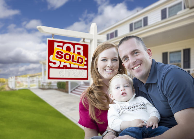 Young Military Family in Front of Sold Sign and House. Happy Young Military Family in Front of Sold Real Estate Sign and New House stock photos