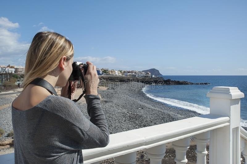 Young millennial female of Caucasian ethnicity holding a professional photo camera and taking pictures of the landscape behind royalty free stock photography