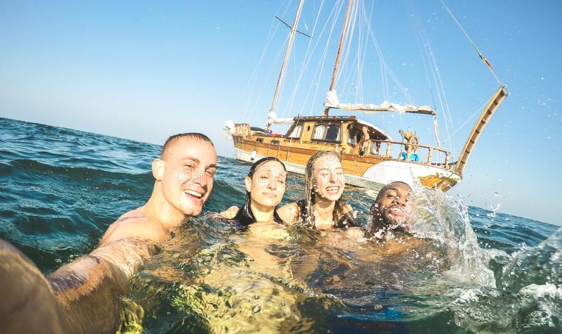 Young millennial friends taking selfie and swimming at sailing boat sea trip - Rich guys and girls having fun in summer party day royalty free stock photos