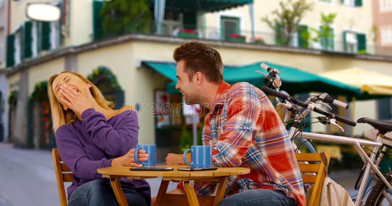 Young millennial laughing at her date`s jokes.  royalty free stock photos