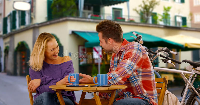 Young millennial laughing at her date`s jokes.  stock photography