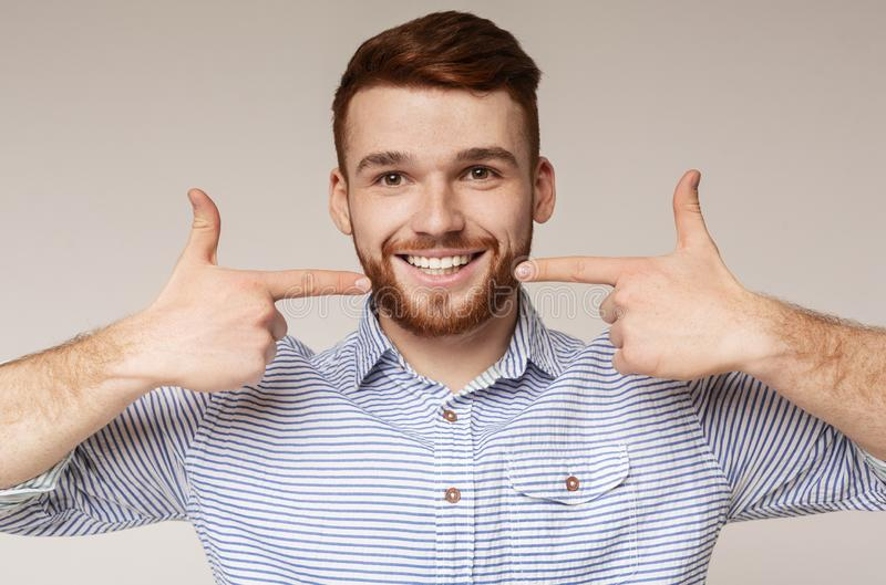 Young millennial man showing his beautiful smile. Dental hygiene. Young millennial man showing his beautiful smile and smooth teeth on beige background, panorama stock photos