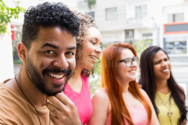 Young millennial people having weekend fun at restaurant outside. Mixed race friends bonding and talking at cafe bar outdoor stock image