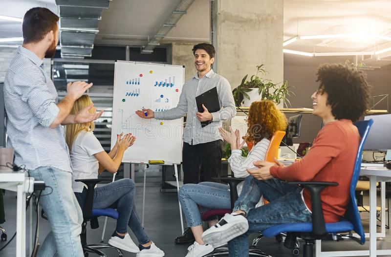Young millennial team analyzing information on graphs and charts stock photos