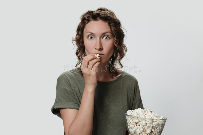 Young millennial woman with curly hair eating popcorn, watching a movie or TV shows stock photography