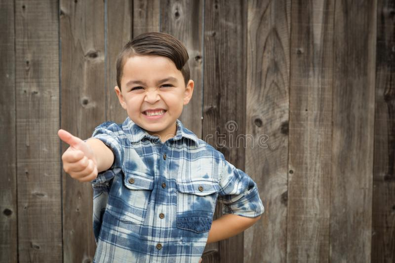 Young Mixed Race Boy Making Hand Gestures. Happy Young Mixed Race Boy Making Thumbs Up Hand Gesture royalty free stock photos