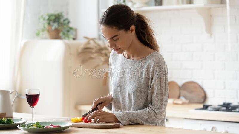 Young mixed race calm woman chopping fresh vegetables for salad. stock photos