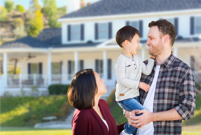 Young Mixed Race Caucasian and Chinese Family In Front of Custom Home. Young Mixed Race Caucasian and Chinese Family In Front of Custom House stock photo