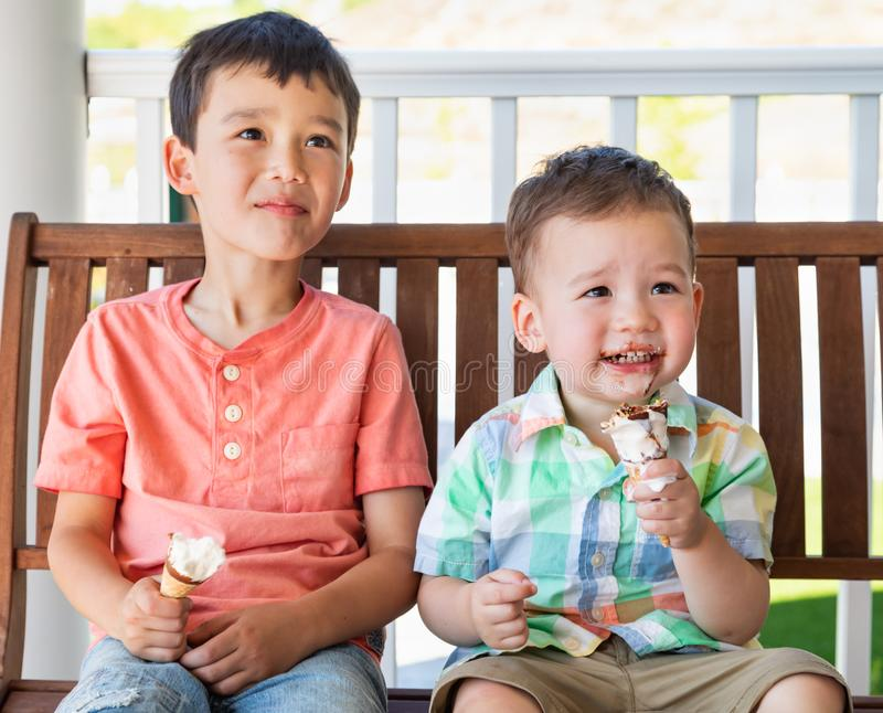 Young Mixed Race Chinese Caucasian Brothers Eating Ice Cream Cones royalty free stock image