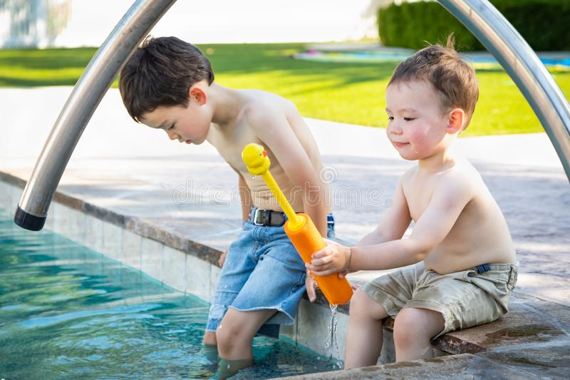 Young Mixed Race Chinese Caucasian Brothers Playing At The Pool stock photography