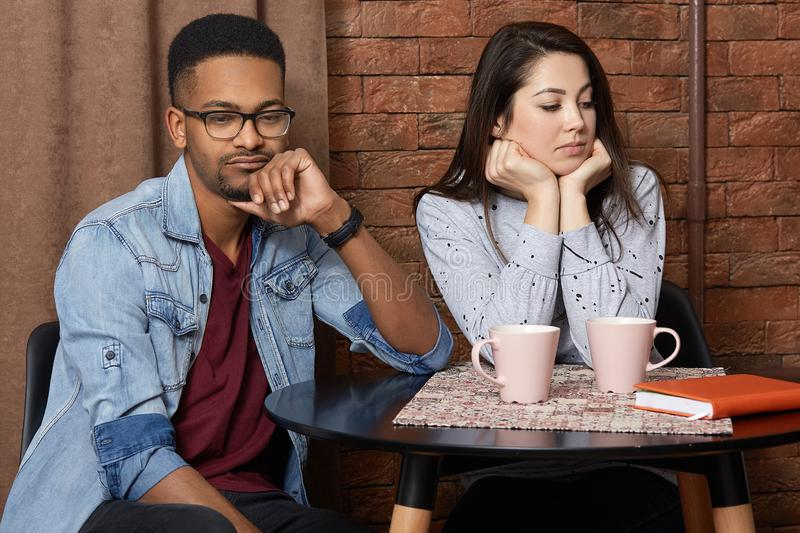Young mixed race couple have quarrel in cafeteria, displeased facial expression, sort out relationships, drink hot coffee, dont stock photo