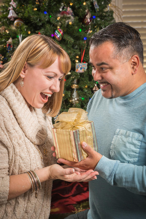 Young Mixed Race Couple with Present Near Christmas Tree. Happy Young Mixed Race Couple with Present Near Christmas Tree royalty free stock photo