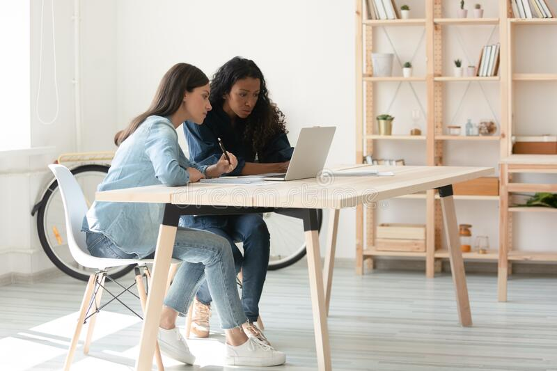 Young mixed race coworkers working on startup project. royalty free stock images