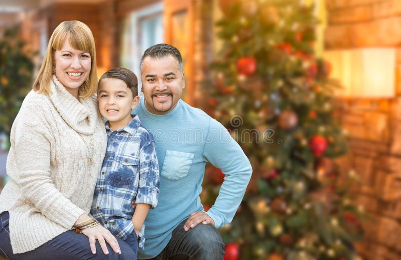 Young Mixed Race Family In Front of Christmas Tree. Happy Young Mixed Race Family Portrait In Front of Christmas Tree Indoors stock image