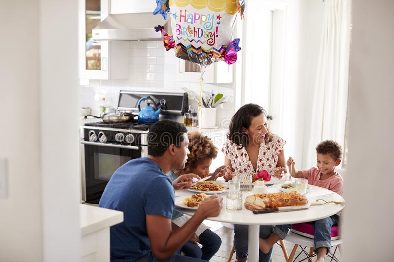 Young African American  family having a birthday meal together at the table in their kitchen, seen from doorway stock photography