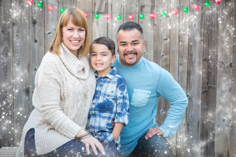 Young Mixed Race Family Holiday Portrait Outside. Happy Young Mixed Race Family Portrait Outside with Christmas Lights and Snow Effect royalty free stock photo