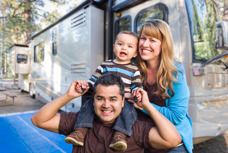 Young Mixed Race Family Traveling in Their Beautiful RV. Happy Young Mixed Race Family In Front of Their Beautiful RV At The Campground stock photos
