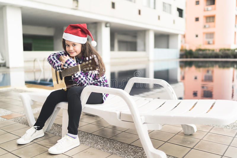 Young mixed race girl with guitar, sitting by swimming pool, with christmas santa hat, music concept stock photography