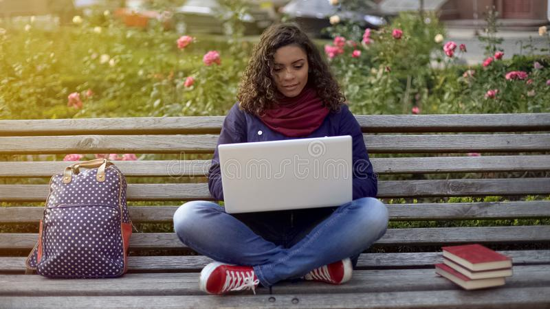 Young mixed race lady writing essay on laptop, studying full of inspiration royalty free stock image