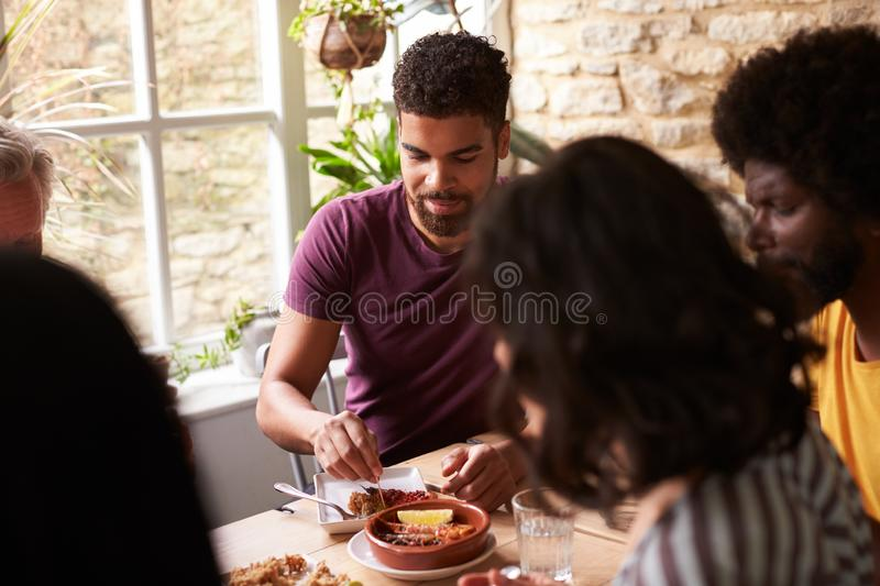 Young mixed race man eating with friends at a dining table stock photos