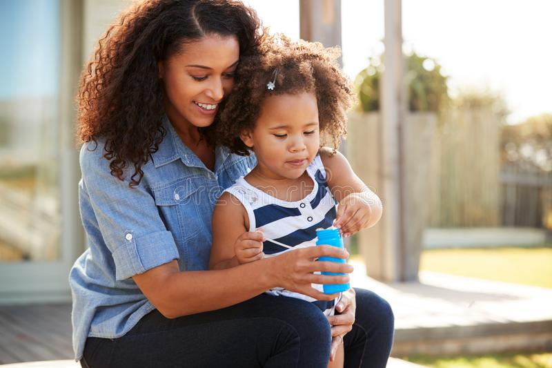 Young mixed race mother and daughter blowing bubbles outside royalty free stock images