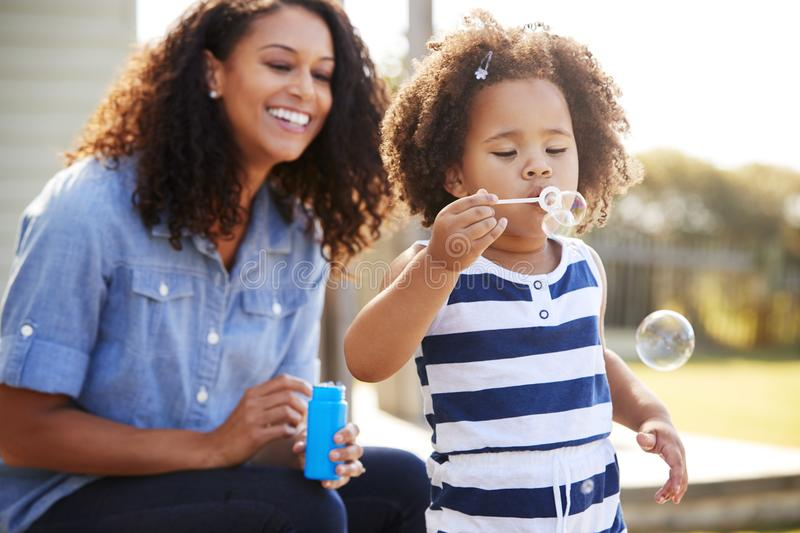 Young mixed race mother and daughter blowing bubbles outside royalty free stock photo