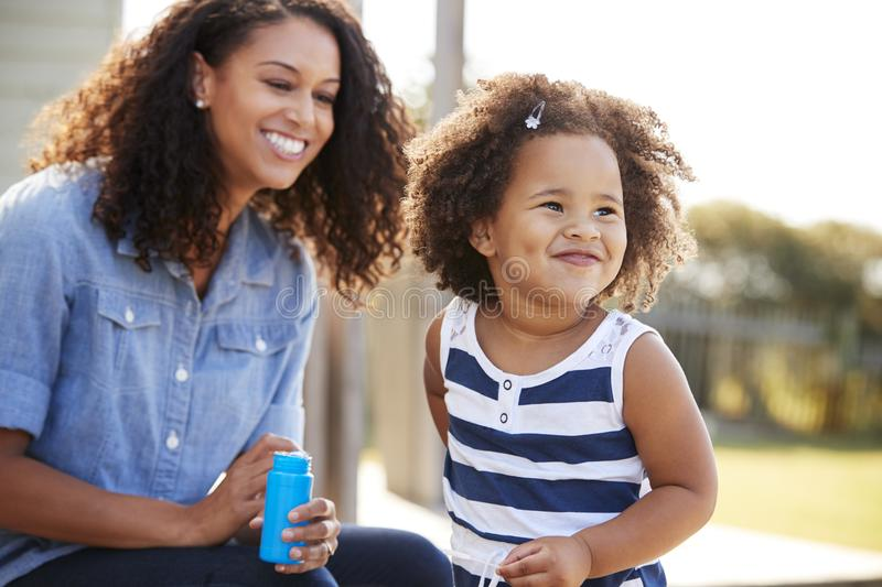 Young mixed race mother and daughter blowing bubbles outside royalty free stock photos