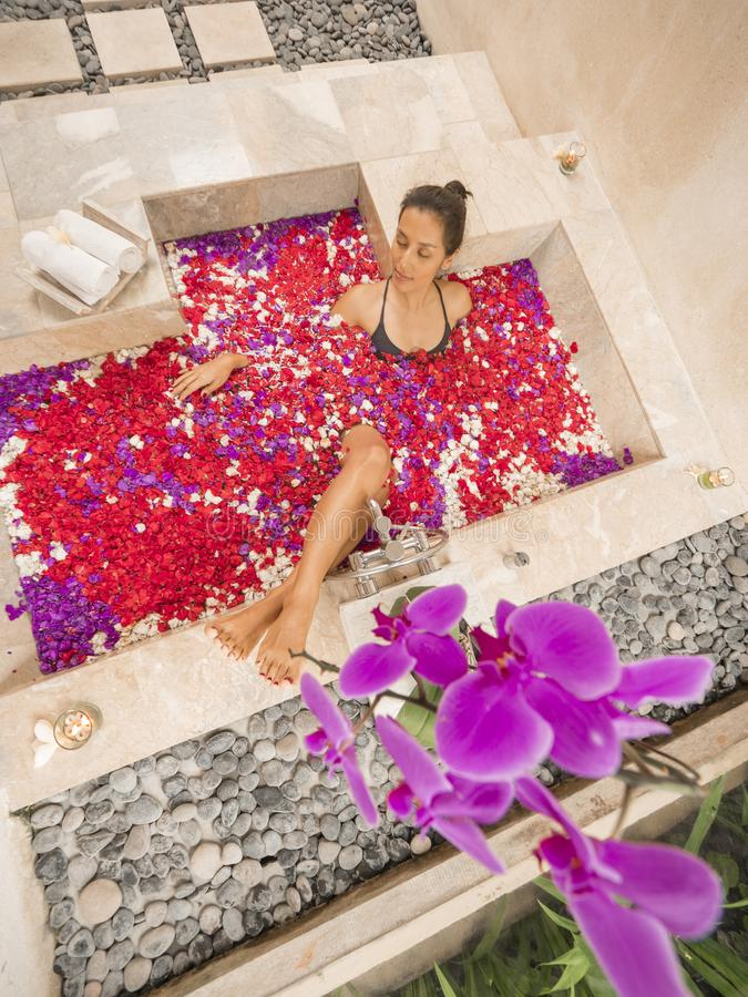 Young Mixed Race Woman Relaxing in Traditional BBalinese Spa Bath Full of Floating Flowers. Bali, Indonesia. stock image
