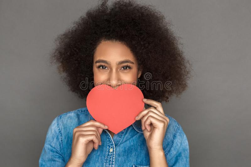 Freestyle. Mulatto woman standing isolated on grey covering mouth with valentine card smiling joyful face close-up stock photo