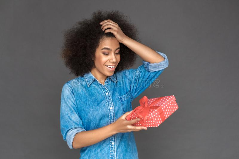 Freestyle. Mulatto woman standing isolated on grey with gift laughing surprised royalty free stock image