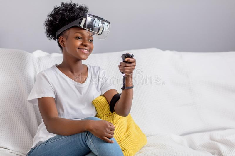 Young mixed race woman wearing virtual reality VR headset on white background. royalty free stock image