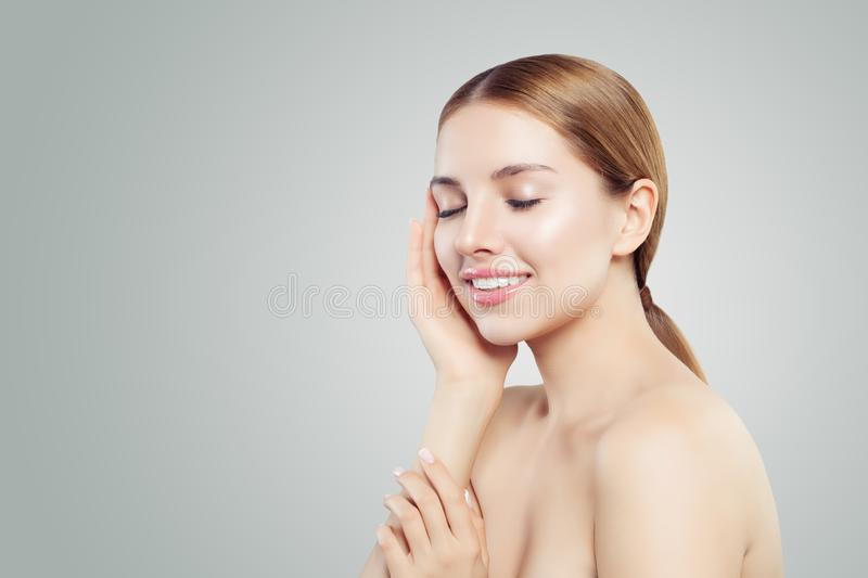 Young model face. Healthy woman smiling on white background, skincare concept stock photos