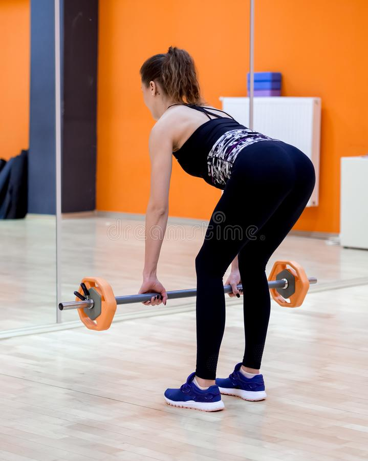 Young model girl makes exercises at the gym in front of mirror. The Young model girl makes exercises at the gym in front of mirror royalty free stock photography