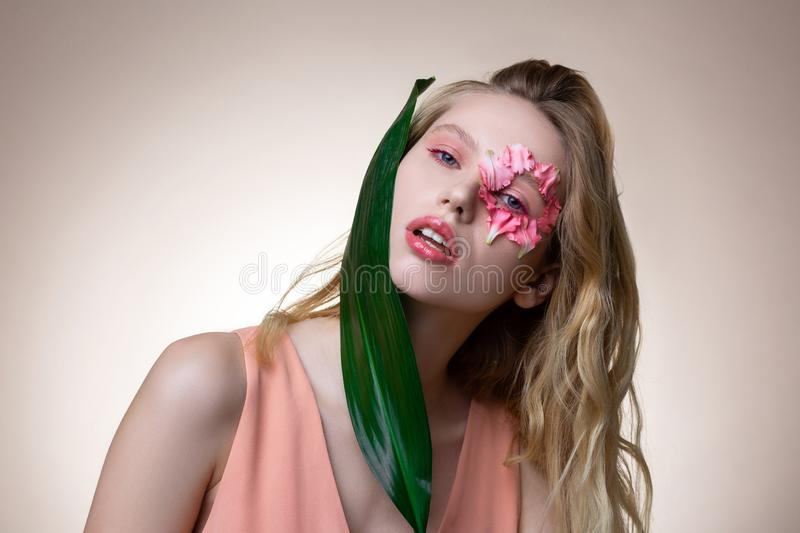 Young model with pink eyeshades posing with leaf and flower. Leaf and flower. Professional young blonde-haired model with pink eyeshades posing with leaf and royalty free stock photos