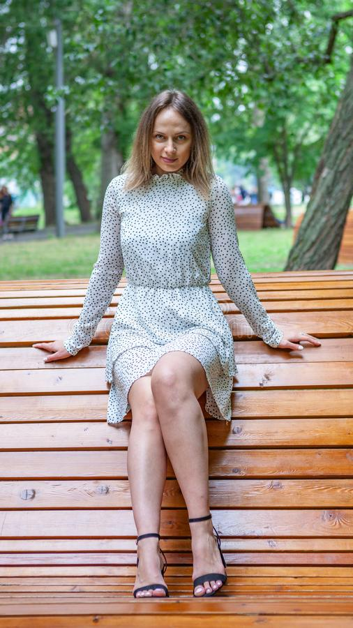 Young model posing on wooden bench royalty free stock photography