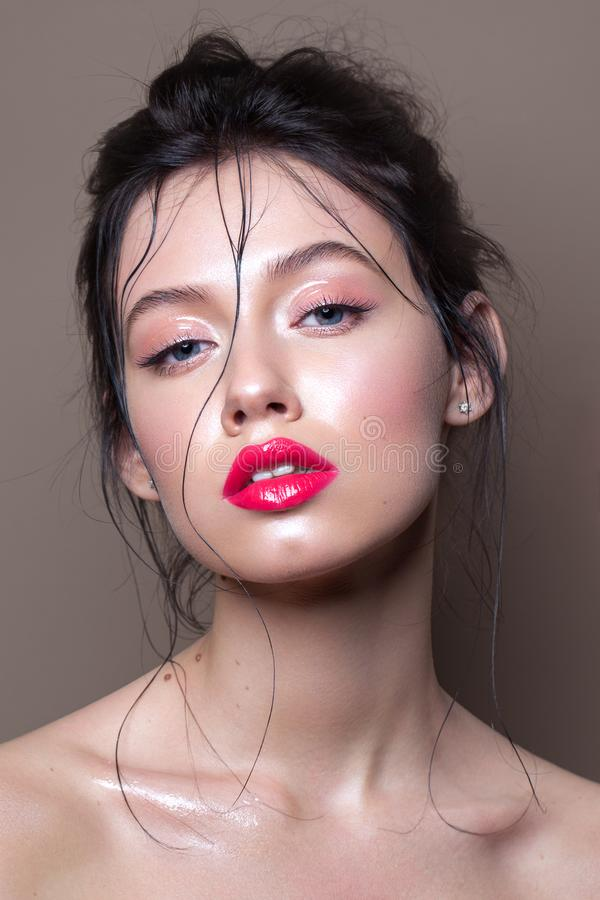 Young model with professional makeup, perfect skin, wet hairdo. Glossy eyelids and glossy red lips stock photo