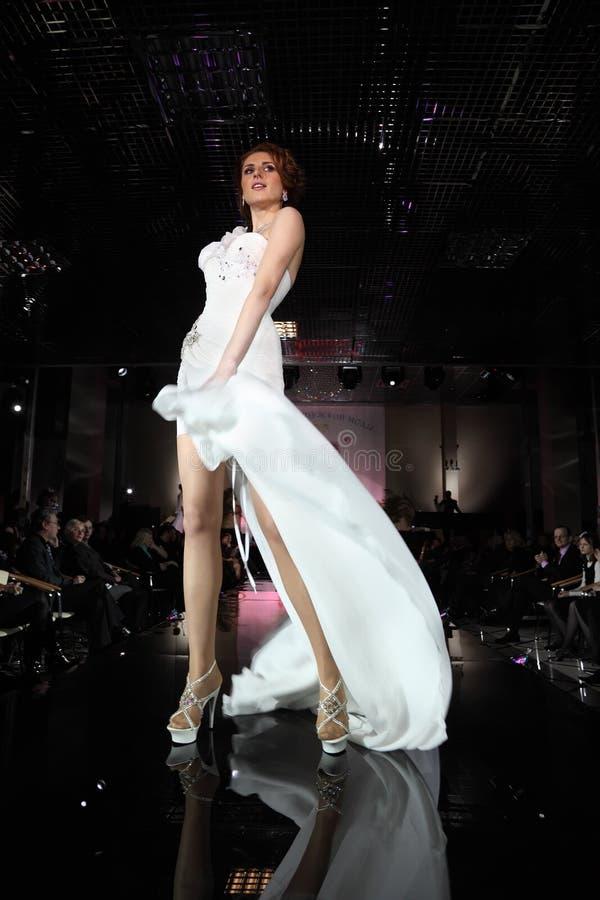 Young model wear white dress walks catwalk royalty free stock photo