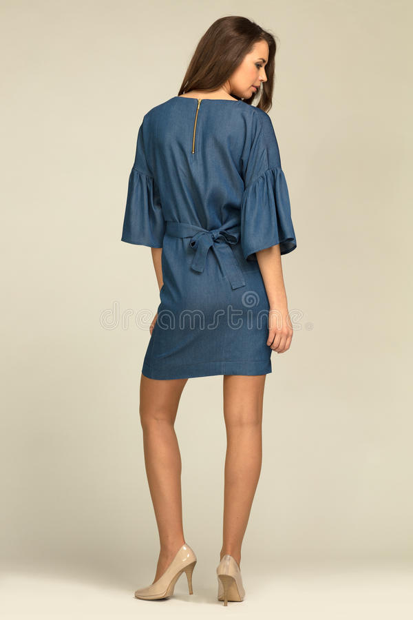 Young model wearing blue, jeans dress with slim body. stock photos