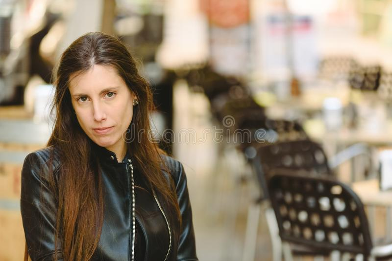 Young model woman with long straight hair wearing leather jacket posing carefree and casual on the street.  royalty free stock photography