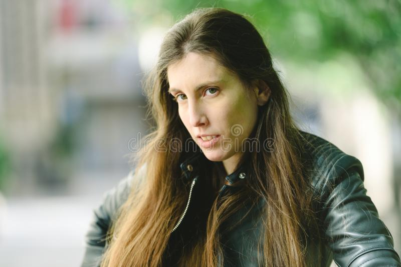 Young model woman with long straight hair wearing leather jacket posing carefree and casual on the street.  stock photography