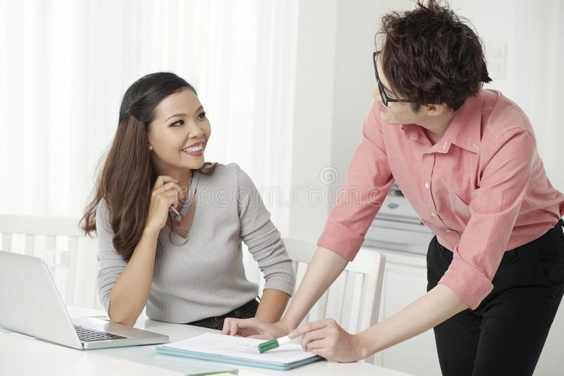 Cheerfu cooperating man and woman in office stock photos