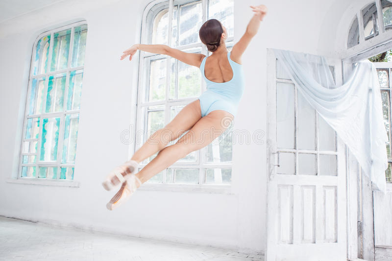 Young modern ballet dancer jumping on white. Young modern ballet dancer jumping or flying on white room background stock photo