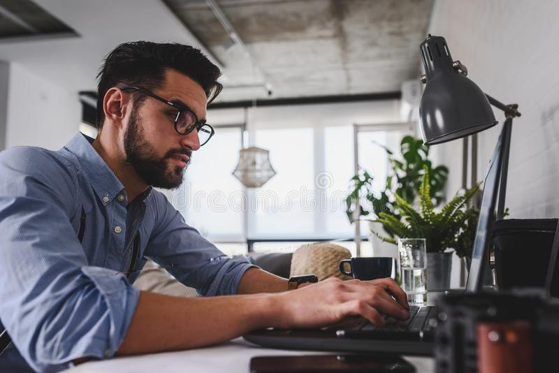 Young bearded businessman is sitting in front of computer, working. Freelancer, entrepreneur works at home. stock image